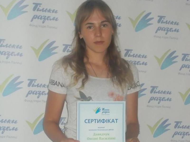 Оксана Давидчук демонструє сертифікат на отримання стипендію від благодійного фонду.....